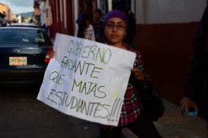 "Protester during the march for the 43 disappeared Ayotzinapa students. The sign reads: ""Treacherous government, killing your students!"" October 2014"